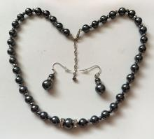 Set of Black color round genuine mother of pearl and hematite faceted beads necklace with two silver tone spacers and channel set white rhinestones and silver tone fish hook and spacers with rhinestones dangling matching earrings.