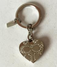 Silver tone key ring with heart shape charm locket and rhinestones, signed COACH