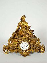 Pendule en bronze ciselé et doré reposant sur trois pieds, la base à décor