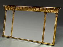 A Regency gilt gesso triple plate mirror, 19th century, with acorn and leaf Gothic top, on Corinthia