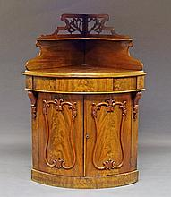 A Victorian mahogany corner cabinet, the raised super structure with pierced foliate decoration, abo