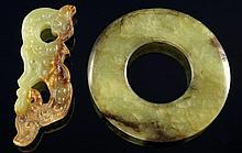 A Chinese carved green and russet jade disk, 6cm w