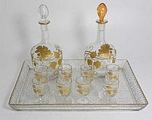Service à liqueur comprenant deux flacons, un plateau, huit verres à pied, décor à l'or fin, circa 1