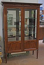 Vitrine en bois de placage ouvrant à deux vantaux, intérieur miroir, piétement fuseau, 135 x 50 x H. 200 cm