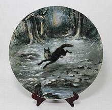 SAINT-AMAND - E. PETIT : Plateau en faïence fine de forme ronde, à décor en plein d'un renard dans un paysage enneigé, signé, début 20e siècle, D. 42 cm