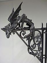 Pierre-François Marie BOULANGER (1813-1891) Exceptionnelle et importante potence décorative, d'inspiration néo-gothique, figurant un dragon ailé à l'évocation d'une gargouille.  L'animal, en ronde-bosse, est exécuté entièrement en fer travaillé et ouvragé à la forge, le corps et la tête d'un seul tenant, les ailes, les pattes, les oreilles et la crête fixées en rivetage.
