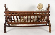 A DOLL CRADLE WITH BABY DOLL