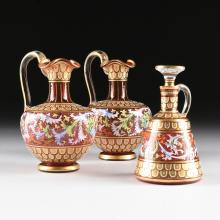 A THREE PIECE BOHEMIAN PARCEL GILT AND POLYCHROME ENAMELED CRANBERRY GLASS SET, POSSIBLY BY MOSER, LATE 19TH/ EARLY 20TH CENTURY,