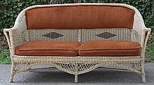 Upholstered painted wicker couch.