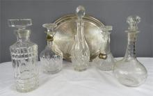 A group of cut glass decanters of varying form and a silver plated tray.
