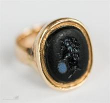 A yellow metal intaglio ring, the black oval intaglio depicting a male prof