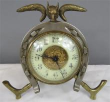 A brass 'Hunt' clock in the form of a horseshoe, whip and fox head finial.