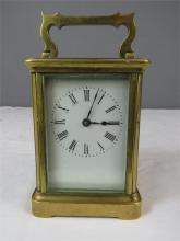 A brass carriage clock with enamelled dial.