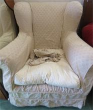 A wing back upholstered armchair with loose cover.