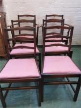 A set of six Ercol chairs including two carvers, bearing blue labels to the