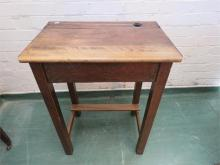 An oak school desk with lid and inkwell to the top.