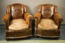 A pair of early 20th century tooled leather armchairs, the backs enriched w