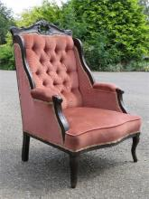 An Edwardian mahogany armchair with carved frame, pink velour button back,