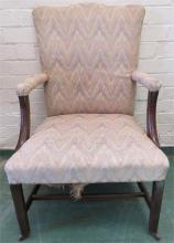 A Georgian mahogany open armchair with shaped and upholstered back.