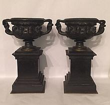 A PAIR OF 19TH CENTURY BRONZE URNS Of Grecian design, raised on black marble bases. (25cm)