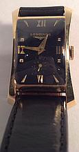 LONGINES, A VINTAGE 14CT GOLD MID SIZE WRISTWATCH Having a rectangular black dial, seconds dial and gilt number markings, on a black leather strap, marked '14k' and contained in a curved case. (approx d 2½cm) 5052/15625/1