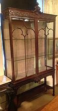 A CHIPPENDALE REVIVAL MAHOGANY DISPLAY CABINET  The shell carved cartouche and scroll carved frieze, above two glazed doors and a lower open shelf, raised on square chamfered legs. (119cm x 215cm) Condition: good