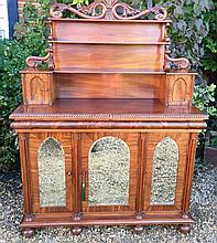 A VICTORIAN MAHOGANY CHIFFONIER The shelved back with scroll supports, carved with acanthus leaves and fitted with two trinket compartments, above three bevelled mirrored doors, separated by cluster columns. (w 128cm x h 167cm x d 40cm) Condition: