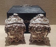 A CASED PAIR OF GEORGE III NEO-ROCOCO CHINOISERIE SILVER TEA CADDIES