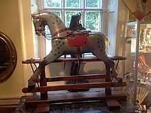 AN EDWARDIAN CARVED WOODEN CHILD'S DAPPLE GREY ROCKING HORSE.