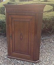 AN EARLY 19TH CENTURY MAHOGANY BOW FRONTED WALL HANGING CORNER CABINET