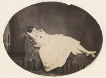 (UNKNOWN PHOTOGRAPHER) A woman posing on a settee.