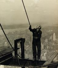 LEWIS W. HINE (1874-1940) Construction worker standing on an I-beam pulling a rope, Empire State Building.