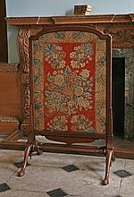 A George III mahogany framed fire screen,   with needlework floral panel, united by square stret