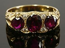 A three stone ruby and diamond carved head ring