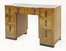 An Art Deco kneehole desk,  the breakfront with a leather top over a ce