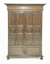 A Gothic oak cupboard,  with panelled doors en
