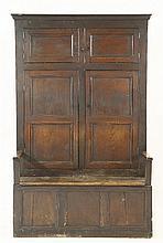 An oak bacon settle,17th century, the tall back w