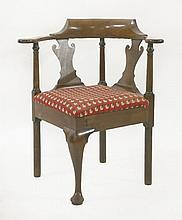 A George II mahogany corner chair,   with solid s
