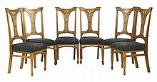 A set of six Art Nouveau oak inlaid dining chairs,