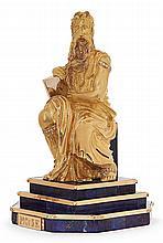 STATUETTE EN OR JAUNE Elle représente Moïse assis tenant sous son bras droit les tables de la loi. Il repose sur une terrasse en dég...