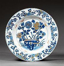 PLAT en porcelaine, bleu de cobalt sous couverte, rouge de fer et dorure, monté sur un petit talon, de forme circulaire, à décor, di...