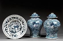 GRAND PLAT CREUX en porcelaine et bleu de cobalt sous couverte, monté sur un petit talon, le contour circulaire, à décor, sur le bas...