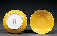 PAIRE DE COUPES en porcelaine et couverte monochrome jaune, de forme circulaire, montée sur un petit pied, à paroi galbée et lèvre é...