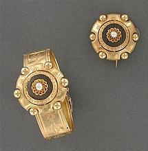 Parure composée d'un bracelet ouvrant articulé et d'une broche au modèle en or jaune gravée et émaillée noir, elle porte au centre u...