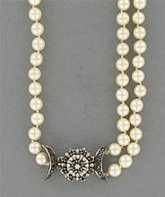 A cultured pearls necklace with a gold sapphire and diamond clasp.