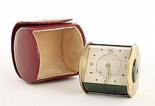 JAEGER REVEIL DE VOYAGE Pendulette cylindrique en laiton doré avec réveil. Cadran beige avec index points et chiffres arabes appliqu...