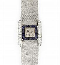 OMEGA VERS 1940 Montre bracelet de dame en or gris avec boîtier rond. Cadran argenté entouré de saphirs calibrés et brancards diaman...