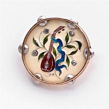 Attribuée à Lucien FALIZE Années 1890 Broche émail Elle est de forme ronde à décor émaillé polychrome d'une mandoline dans un bouque...