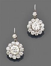 Paire de boucles d'oreilles dormeuses marguerite faites de deux marguerites serties chacune d'un diamant surmonté d'un petit diamant...