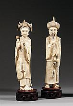 PAIRE DE STATUETTES DE DIGNITAIRES en ivoire et rehauts d'encre, représentés en pied, l'un tenant un sceptre ruyi, l'autre portant u...
